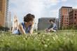 Deutschland, Berlin, Junge Frau liegt auf der Wiese hält Handy, Mann im Hintergrund