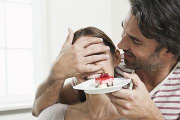 Deutschland, Berlin, Mann überrascht Frau mit Kuchen serviert