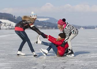 Österreich, Teenager-Mädchen auf der Eisbahn, Freunde helfen ihr hoch