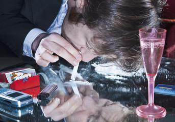Junger Mann schnupft Kokain