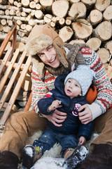 Österreich, Land Salzburg, Flachau, Junger Vater mit Sohn sitzt vor Lagerfeuer