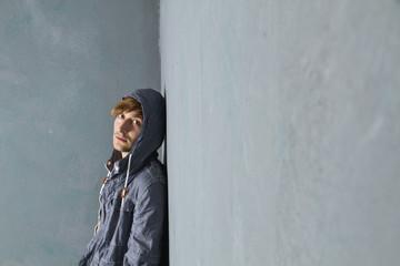 Junger Mann stehen an schmutzige Wand gelehnt