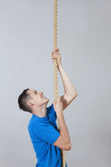 Deutschland, Berlin, Junger Mann an einem Kletterseil in Turnhalle