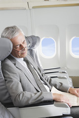 Deutschland, Bayern, München, Älterer Geschäftsmann, Schlafen in der Business Class Flugzeugkabine