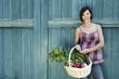 Deutschland, Bayern, Frau steht vor Stalltür, hält Korb mit frischem Gemüse