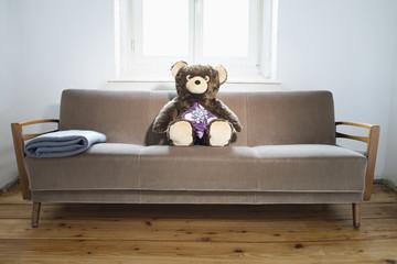 Teddy auf dem Sofa mit Geschenkpaket