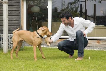 Junger Mann spielt mit Hund im Garten