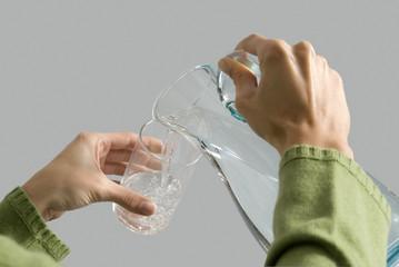 Junge Frau gießt Wasser aus Krug in Glas