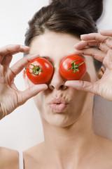 Brunette Frau mit Tomaten auf den Augen