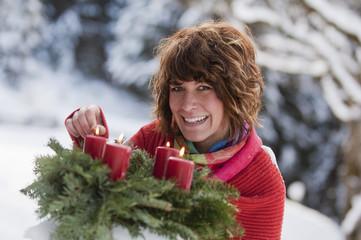 Österreich, Land Salzburg, Flachau, Junge Frau zündet Kerzen am Adventskranzan