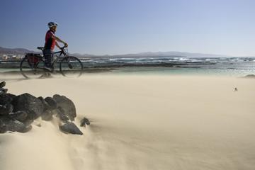 Spanien, die Kanarischen Inseln, Mann mit Mountainbike in einem Sandsturm