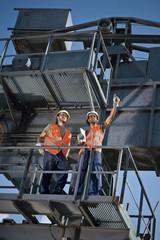 Deutschland, Augsburg, Zwei Arbeiter stehen auf große Maschine