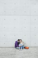 Deutschland, Berlin, Paar sitzt vor der großen Wand auf Bürgersteig