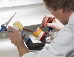 Zahnarzt arbeitet an Zahnersatz in zahntechnischen Labor