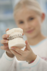 Deutschland, Bayern, Landsberg, Mädchen hält Zahnmodell mit Zahnspange