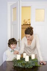 Mutter und Sohn zünden Adventskranz an