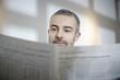 Deutschland, Köln, erwachsener Mann liest Zeitung