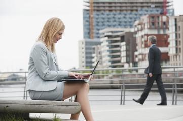Deutschland, Hamburg, Geschäftsfrau mit Laptop, Mann zu Fuß im Hintergrund