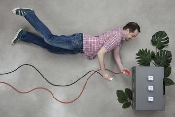 Mann,steckt zwei Stecker in eine Steckdose aus Pflanzen