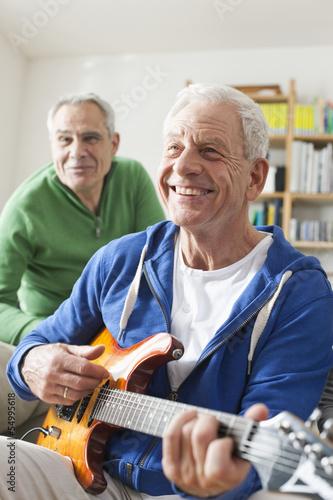 Deutschland, Leipzig, Senior, Rentner spielt E-Gitarre, Mann sitzt im Hintergrund