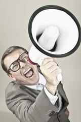 Nahaufnahme Geschäftsmann schreiend durch Megaphon gegen grauen Hintergrund