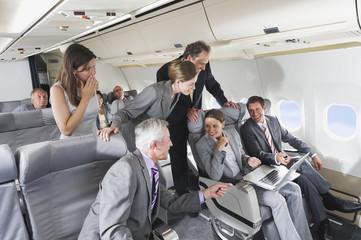 Deutschland, Bayern, München, Gruppe von Passagieren mit Laptop in der Business Class Flugzeugkabine