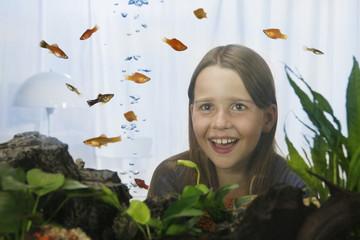 Mädchen beobachtet Fische im Aquarium