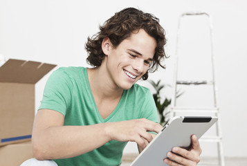 Deutschland, Köln, Junger Mann mit Tablet-PC, iPad beim Umzug