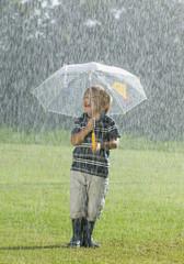 Junge stehend mit Regenschirm im Regen