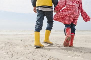 Deutschland, Nordsee, St.Peter-Ording, Kinder tragen Stiefel und Regenmäntel, zu Fuß am Strand