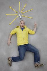 Junger Mann zeigt auf Glühbirne