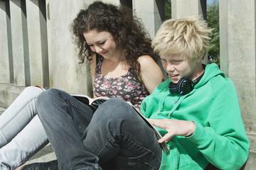 Deutschland, Berlin, Teenage Paar sitzt auf der Brücke und Lesen
