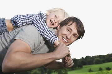 Deutschland, Köln, Vater trägt Sohn Huckepack
