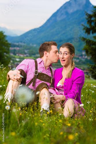 Paar in Tracht auf Wiese vor Berg mit Kuss