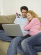 Paar auf dem Sofa, Frau beobachtet Mann mit Laptop