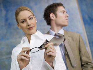 Geschäftsfrau, Reinigung der Brille mit Krawatte des Mannes