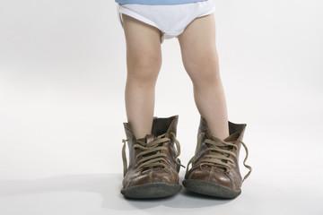 Kind trägt große Schuhe