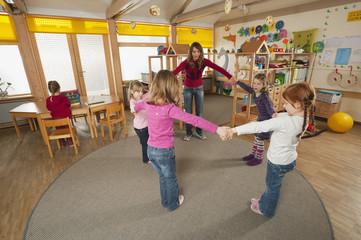 Deutschland, Babyzimmer,Kindergärtnerin und Kinder tanzen