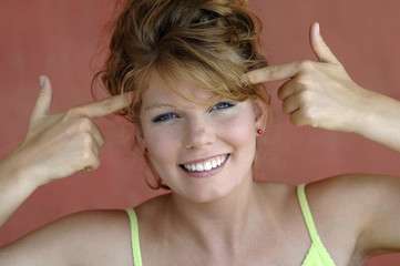 Junge Frau hält Zeigefinger an den Kopf