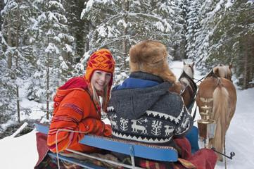 Österreich, Salzburger Land, Paar fährt im Pferdeschlitten, Lächeln