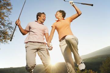 Italien, Kastelruth, Paar mittleren Alters gemeinsam springend