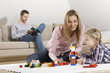 Vater mit Lesebuch, Mutter und Tochter spielen im Vordergrund