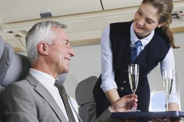 Deutschland, Bayern, München, junge Stewardess serviert Champagner in Business-Class-Flugzeugkabine