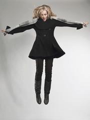Frau springt vor grauem Hintergrund und Blick nach unten
