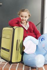 Deutschland, Leipzig, Mädchen mit gepackten Koffern