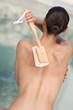 Frau wäscht sich den Rücken mit einer Bürste