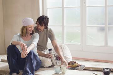 Junges Paar auf der Baustelle, eine Pause machend