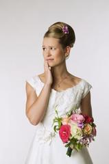 Junge Braut mit Brautstrauß, Hand an Kinn
