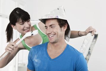 Deutschland, Köln, Junges Paar Spaß beim Malen , Wohnungsrenovierung