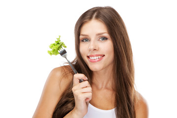 Young woman eating green salad